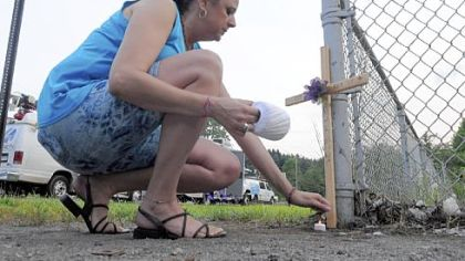 Tina Smith, of Monaca, places a cross outside the Horsehead Corp. plant on Thursday evening.