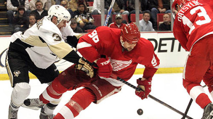 Red Wings forwards Tomas Holmstrom and Pavel Datsyuk battle for the puck with Penguins defenseman Alex Goligoski during the second period.
