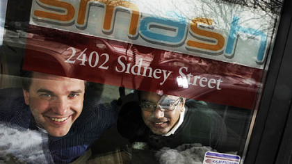 Eric Boduch, left, and Chanakya Damarla, co-founders of Smash, look through their front office door on the South Side.  Smash deals with text messaging on the phone in business.