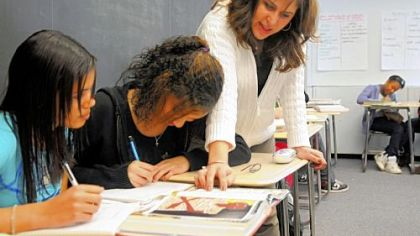 Danielle Harris, a reading coach at Pittsburgh Classical Academy, helps students Brooklynne Smith, left, and Elissa Edmunds with work in Mike Nolf's eighth-grade communications class.