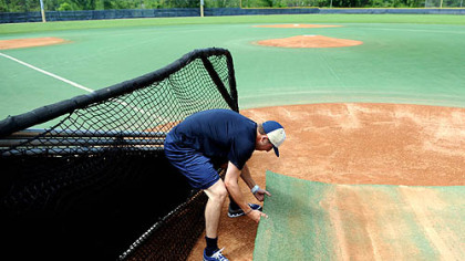 Pitt player Corey Baker pulls a mat over home plate while preparing Trees Field for the weekend series vs. South Florida, the Panthers' final games at Trees Field.