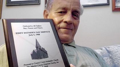 The Rev. D.D. Meighen holds a plaque commemorating the first Father's Day service in memory  of those who died in the Monongah mine explosion.