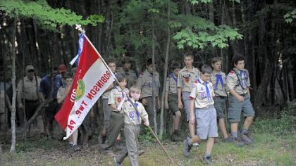 Drake Palmer, 12, of Troop 301 in Robinson, carries the flag to the flag-lowering ceremony at Camp Liberty.