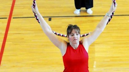 Three aerobics students stretch using hula hoops during a fitness class that combines hooping and Pilates at the Peters Township Community Recreation Center.