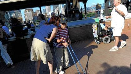 Julie Leckenby of Mt. Lebanon speaks to her son, Joseph Leckenby, 11, as they watch a performance at the street festival at Station Square on Monday that followed a community forum marking the 20th anniversary of the signing of the Americans with Disabilities Act.