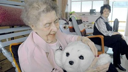 Millie Lesek, 89, pats Paro, a $6,000 furry robot at Vincentian Home in McCandless. At right is Eileen Oldaker, her daughter.