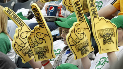Pirates fans wave foam rubber hands and wear green ball caps as they cheer in the sixth inning.