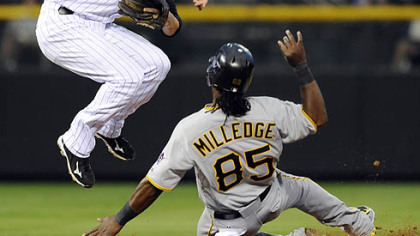 The Pirates' Lastings Milledge slides into second after being forced as Rockies second baseman Clint Barmes throws to first base to turn the double play on the Pirates' Ronny Cedeno in the sixth inning.