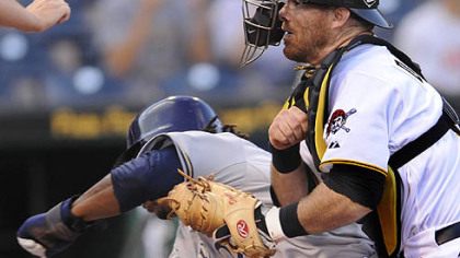 The Brewers' Rickie Weeks runs into Pirates catcher Ryan Doumit at home plate in the first inning Wednesday at PNC Park. Weeks was safe, and Doumit soon would leave the game.