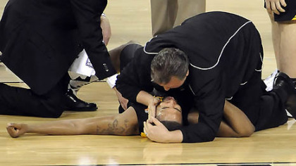 West Virginia coach Bob Huggins comforts Da'Sean Butler after Butler injured his leg against Duke in the second half of the semifinal game in the NCAA tournament in Indianapolis last night.