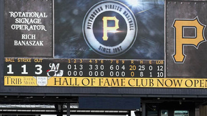 The scoreboard shows the historic final tally as the Brewers go through their post-victory line Thursday at PNC Park.