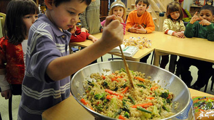 Kindergartner Asher King works on a stir-fry at the Kentucky Avenue School in Shadyside last week.