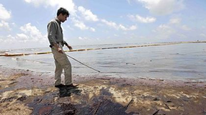 Louisiana Gov. Bobby Jindal walks through oil that got past booms as he tours a land bridge built by the Louisiana National Guard on Friday in Grand Isle, La.