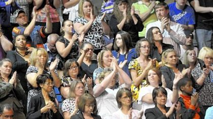 Mourners applaud during Sunday's service.