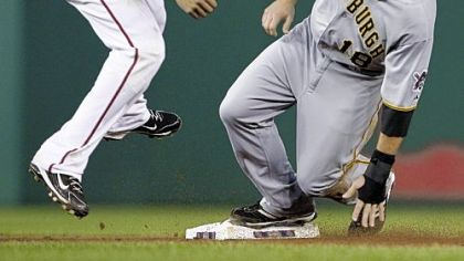 The Pirates' Neil Walker beats Nationals shortstop Ian Desmond to second base before continuing to third base on Nationals catcher Will Nieves' throwing error during the fourth inning of Wednesday's game at Nationals Park in Washington.