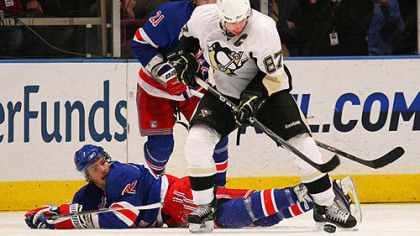 Penguins forward Sidney Crosby and Rangers forward Artem Anisimov battle for control of the puck.