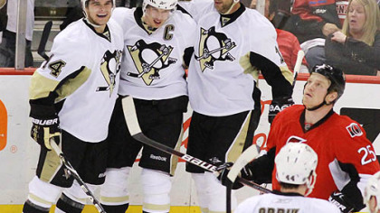 Sidney Crosby, center, celebrates one of his two second-period goals with teammates Chris Kunitz, left, and Bill Guerin as Ottawa's Chris Neil looks on. The Penguins scored five goals in the period en route to a 7-4 victory in Game 4 at Scotiabank Place in Ottawa.