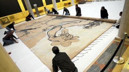 "Ellen Baxter, chief conservator at the Carnegie Museum of Art, inspects Salvador Dali's 1942 stage curtain ""Theseus Minotaur,"" which he painted for the Ballet Russe de Monte Carlo, after it was unrolled in the Hall of Sculpture for the first time in late December."