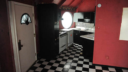 The compact kitchen has bright-red walls, black wood cabinetry and a vintage black-and-white checkered linoleum floor.