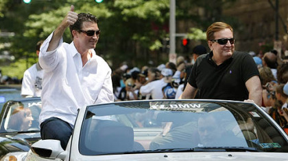 Mario Lemieux, left, and Ron Burkle ride together in the Stanley Cup parade last June.