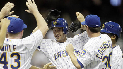 The Brewers' Ryan Braun is mobbed by teammates after getting the game-winning hit during the 10th inning.