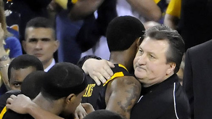 West Virginia coach Bob Huggins hugs Devin Ebanks near the end of his team's loss to Duke in the semifinal game in the NCAA tournament in Indianapolis last night.