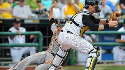 The Giants' Freddy Sanchez slides past Pirates catcher Ryan Doumit in the fifth inning Sunday at PNC Park.
