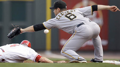 Pirates first baseman Jeff Clement misses a pickoff throw from pitcher Ross Ohlendorf as the Reds&#039; Drew Stubbs dives safely back to first base in the second inning. Clement was charged with an error allowing Stubbs to advance to second.