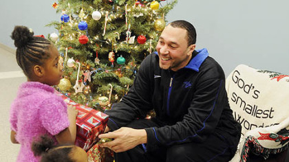 Steelers player Charlie Batch gives a present to Shaterra Lee, 5, who is at the Salvation Army with her mother as part of the Best of the Batch Foundation activities.