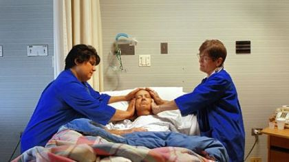 Volunteers Jeanne Weideman, left, and Liz Tafel-Hurley apply hands and pressure to Harriet Krystopolski as part of a Reiki treatment for pain at Allegheny General Hospital.
