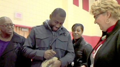 Aliquippa native Darrelle Revis of the New York Jets signs a football at Aliquippa Elementary School on Monday.