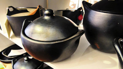 Various types of black clay cooking vessels sit on shelves inside the Annex Cookery store in Homestead.
