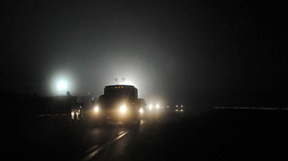 Vehicles pass giant flood lights illuminating an entrance to Massey Energy Upper Big Branch mine in Raleigh County after an explosion there killed at least 25 people, Monday.