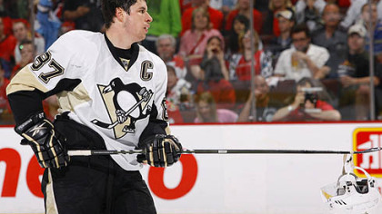 Penguins captain Sidney Crosby picks up his helmet after a scrum during Saturday's game at ScotiaBank Place in Ottawa.