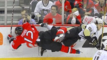 Ottawa's Mike Fisher, left, and the Penguins' Kris Letang crash off each other and the boards early Tuesday night in Ottawa.