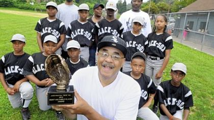 Ron Hill shows off the MVP trophy he will give to a player on the Wilkinsburg Black Sox baseball team that he sponsors.  Mr. Hill discovered that his great uncle, John Preston Hill, is the Pete Hill who was named to the Baseball Hall of Fame in 2006, but his name is incorrectly recorded on the plaque in Cooperstown.