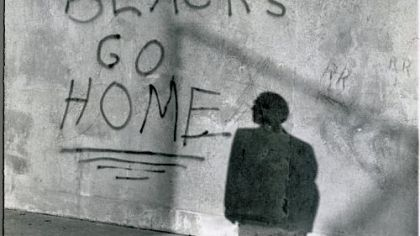 A bystander reads graffiti on the wall of a school in Glendale, N.Y., on Sept. 14, 1959, after black students were transferred from schools in the Bedford-Stuyvesant area of Brooklyn to the predominantly white Queens school.
