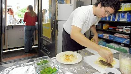 At the Kubideh Kitchen, Angel Gonzalez prepares kubideh sandwiches, an Iranian dish of spiced ground beef served with fresh basil, mint and onion on homemade Barbari bread with black sesame seeds.