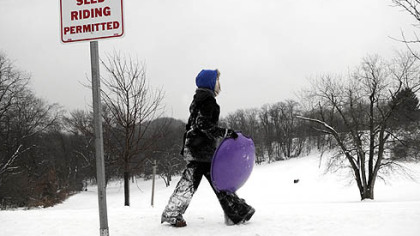A sledder scouts for a spot to sled down the hill yesterday at Frick Park in Squirrel Hill.