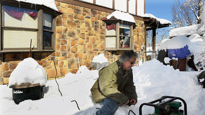 Gene Conti checks on the 2,500-watt generator powering appliances in his Stafford St. home in Pittsburgh&#039;s Sheraden neighborhood Monday afternoon. His home has been without electricity since Friday night.