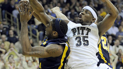 Pitt forward Nasir Robinson gets tangled up with West Virginia forward John Flowers in the first half.