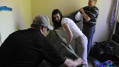 Andrew Lambl, a volunteer from Murrysville, arranges some bedding while Andrea Germansky, a first-grade teacher at Pittsburgh Schaeffer K-8 school, reaches for items to place on J'Quinn Johnson's bed in her Crafton Heights home.