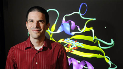 Dr. Markus Dittrich stands in front of a rendition of a photo receptor protein. The biomedical scientist at the National Resource for Biomedical Supercomputing at the Pittsburgh Supercomputing Center based in Oakland will help oversee Anton's operation.
