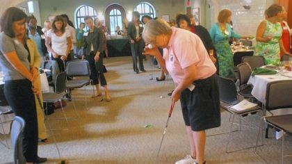 Sandy Thomas demonstrates a trick about putting stance for a women's entrepreneurship luncheon Tuesday at Chatham University: Hold a ball to your eye, let it drop, and if you are in the correct stance over the ball, the falling ball will hit the one on the ground.