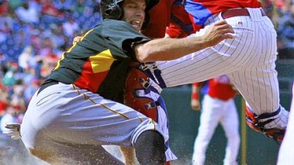 Jim Negrych, a Pitt graduate and member of Class AA Altoona, scores for the Pirates in the eighth inning Saturday, sliding past the tag of Phillies catcher Paul Hoover.