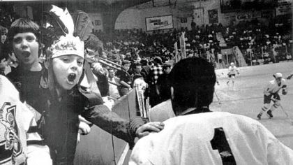 Juliette Slonka, age 7, gives Chiefs goaltender Bob Deraney a pat on the back as Deraney returns to the ice.