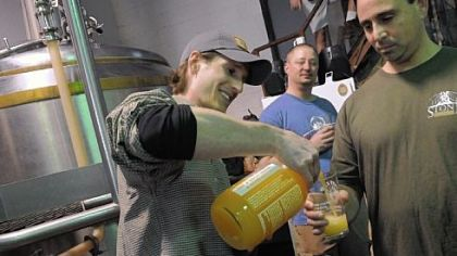 Joe Green, a volunteer with East End Brewing Co., pours a beer for Adam Cratty of Oakmont.