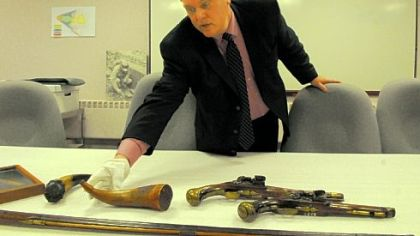 Fort Pitt Museum Director Alan Gutchess works with the display of powder horns and pistols as  the museum prepares to reopen Saturday.