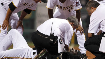 The Pirates&#039; Andrew McCutchen is cared for by trainers Brad Henderson, bottom center, and Mike Sandoval, right, with manager John Russell, left, coach Tony Beasley, top center, during the second inning.
