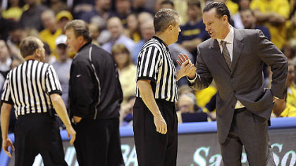 West Virginia head coach Bob Huggins, left, and Pitt coach Jamie Dixon talk with officials after a tussle between players occurred in the second half of Wednesday's game in Morgantown W.Va. Fans threw debris on the court twice during the contest.